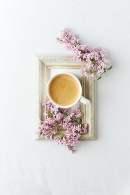 Cup of coffee, lilac branch and frame on white background. Flat