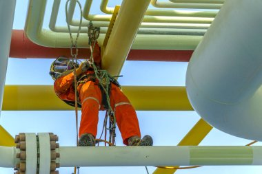 Working at height. An abseiler from front view with dirty coverall wearing Personal Protective Equipment (PPE) hanging at life lines stepping on pipeline managing his rope access stock vector