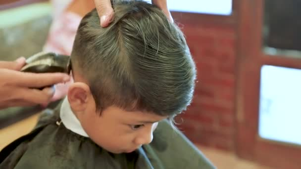 Kid haircut with scissors and razor. Close up of hair trimmer hairstyle by professional hair stylist.