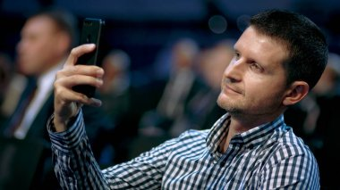 Person taking photography phone. Business man listen lecture in crowd audience.