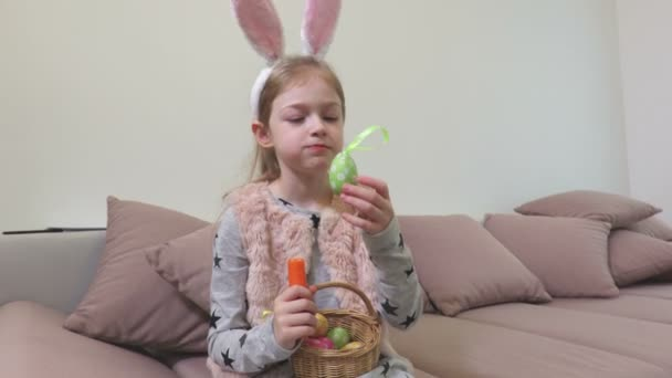Girl with bunny ears and decorative Easter eggs eating carrot