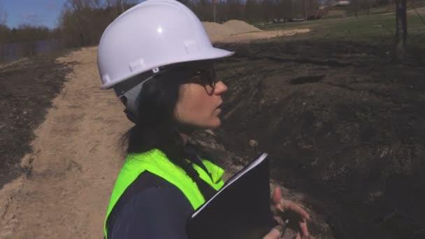 Žena inženýr chůzi a hovoří o staveniště