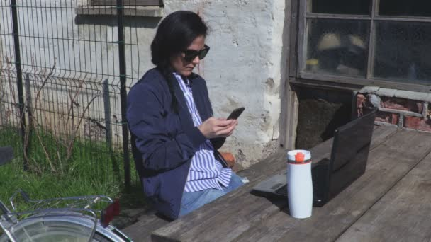 Woman using phone near Pc on table