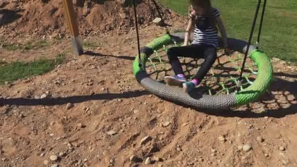 Little girl is swinging on swings