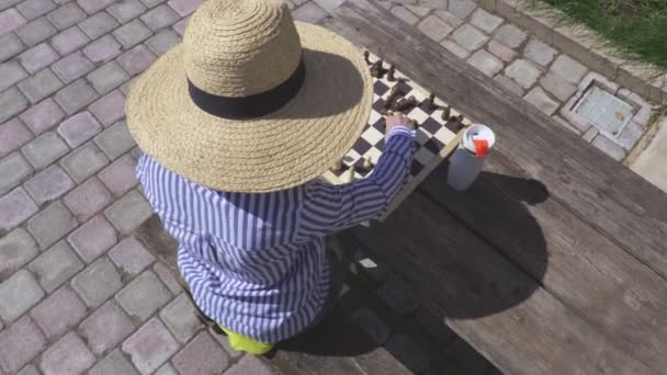 Woman in straw hat near table with chess
