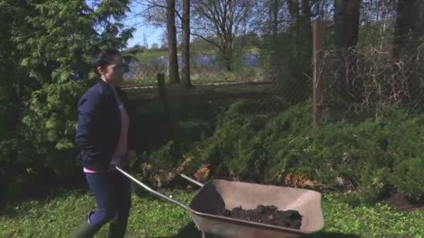 Frau drängen Schubkarre im Garten
