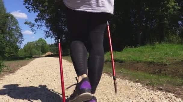 Camera follow woman hiker with Nordic walking poles