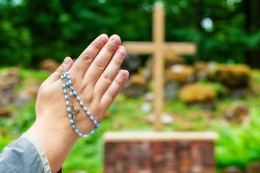 Hands with rosary praying near cross at outdoor