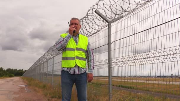 Ochranka pomocí vysílačku poblíž drátěný plot