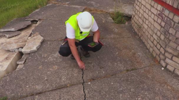 Építőmunkás fog fénykép-ra tabletta-on a repedt beton födém