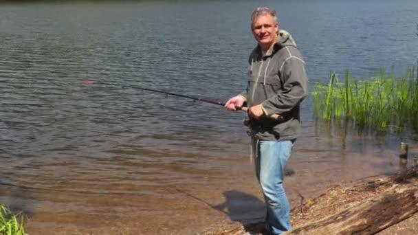 Šťastný muž s rybářský prut u jezera