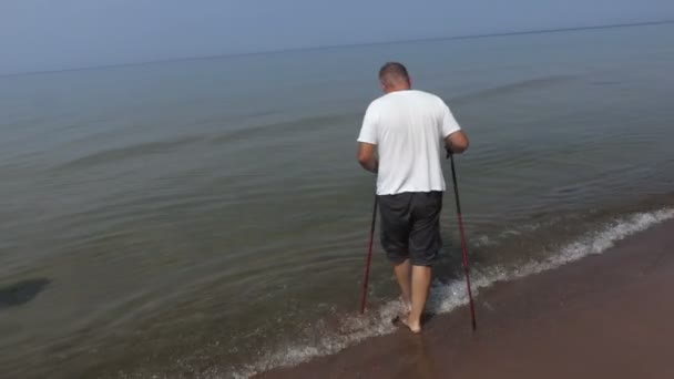 Man with walking poles slowly walk in the water