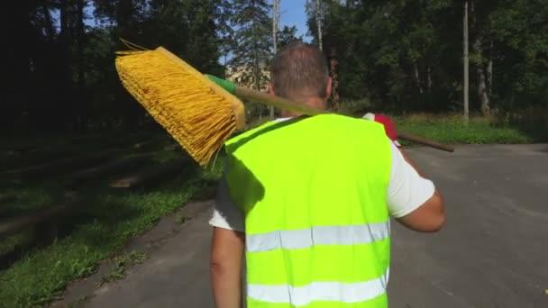 Pracovník s kartáčem, procházky v parku