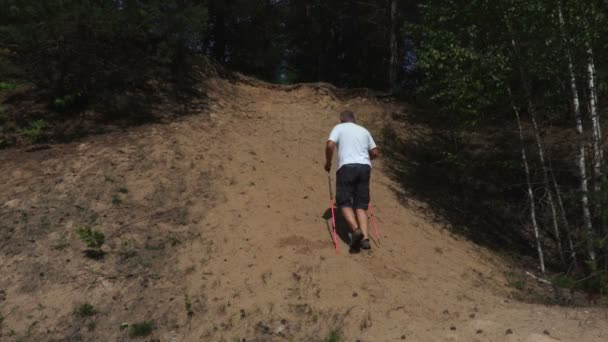 Hiker with walking poles and binoculars climb a  hill