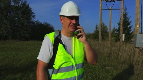 Elektrikář s smartphone v transformátoru