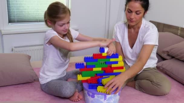 Matka a dcera hrát s barevnými hračka cihly