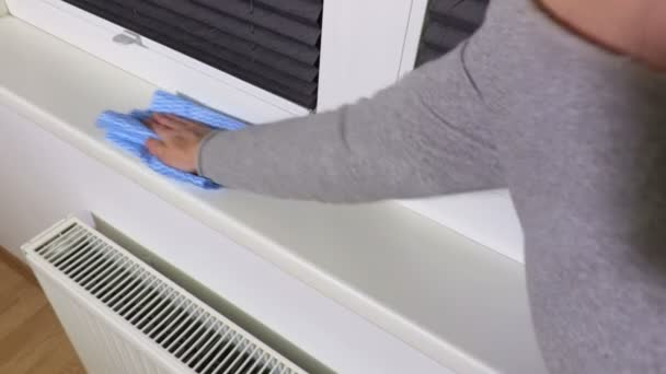 Žena čištění okenní parapet