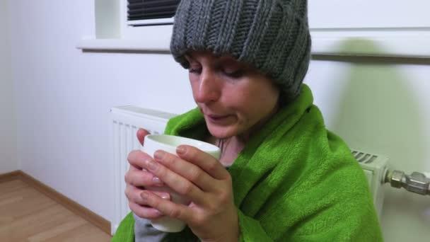 Woman with cup of tea warming near heating radiator
