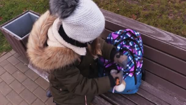 School girl child checking backpack on bench