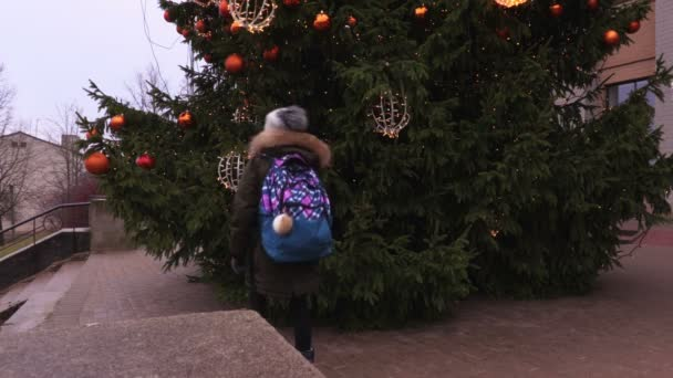 School girl with backpack watching Christmas tree decorations