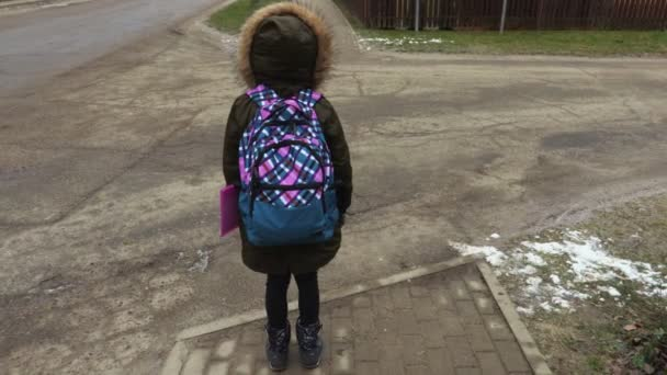 Little girl with backpack after school try to cross the road