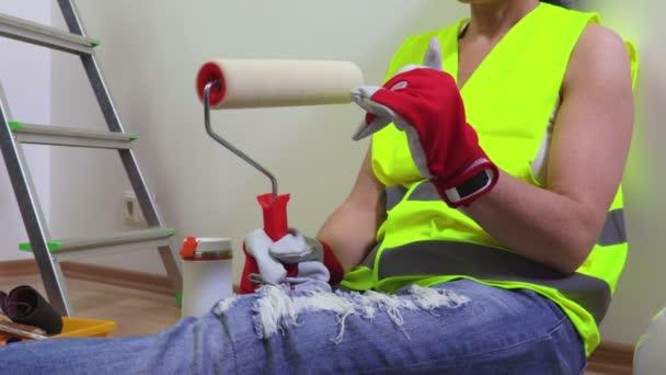 Bauarbeiterin mit Malerrolle