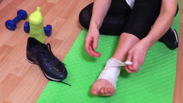 Woman on fitness mat fixing medical bandage on painful ankle