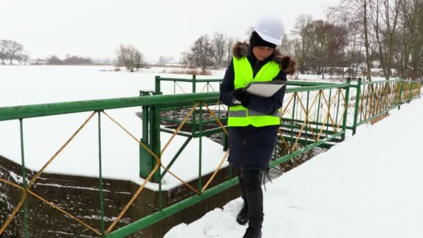 Woman engineer writing and walking on bridge near sluices