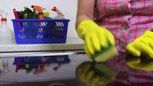 Žena čistý elektrický sporák povrch v kuchyni