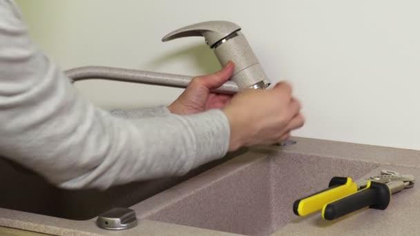 Frau fixiert Wasserhahn auf Küchenspüle