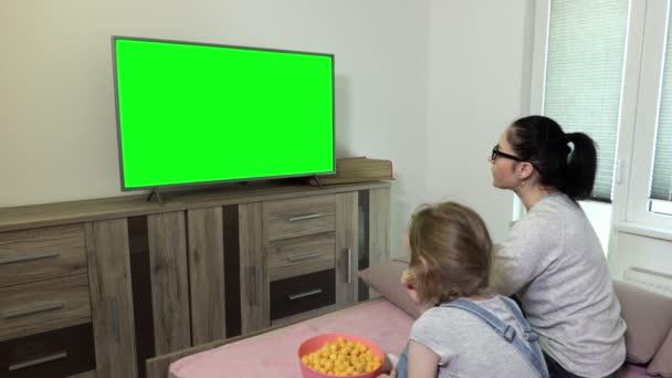Dcera a matka jedí křupky z mísy a používají dálkové ovládání v blízkosti televize se zelenou obrazovkou