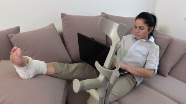 Behinderte Frau mit Krücken liegt im Bett und benutzt Laptop