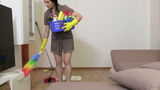 Uklízečka drží čistící prostředky a uklízí nábytek doma