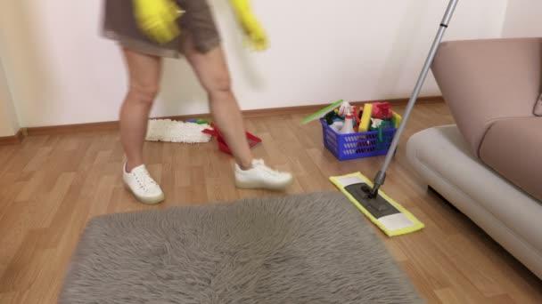 Žena v rukavicích čistí podlahu a falešný kožešinový koberec