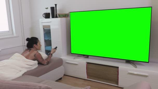 Žena ležící na pohovce a dívat se na zelenou obrazovku televize