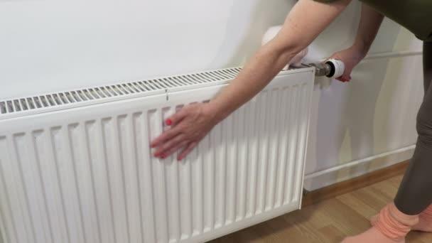 Frau inspiziert Erwärmung des Heizkörpers. Energiesparkonzept