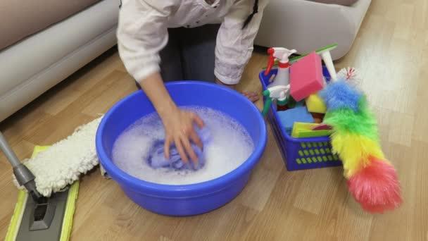Žena čistič s hadrem v blízkosti plastové nádoby s vodou
