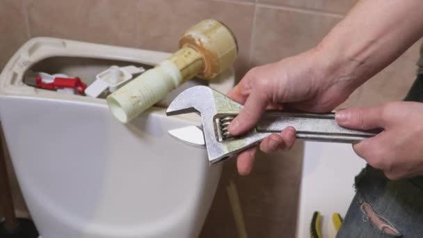 Konzept der Frau Klempner Befestigung einstellbaren Schraubenschlüssel in der Nähe der Toilette Zisterne bei Wasser Toilette