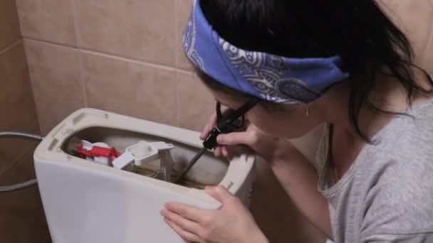Žena poblíž záchodové nádrže se snaží najít poškození