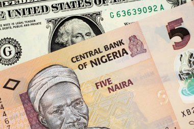 An orange Nigerian 5 naira note with an American one dollar bill
