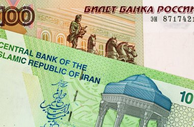 A close up image of an Iranian 10000 rial note with a Russian 100 ruble bank note