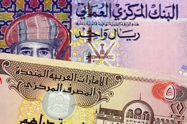 A close up image of an Omani one rial note with a United Arab Emirates five Dirham bill