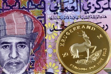 A close up image of a colorful Omani one rial bank note with a gold krugerrand coin