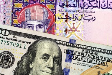 A colorful Omani one rial note with an American one hundred dollar bill in macro