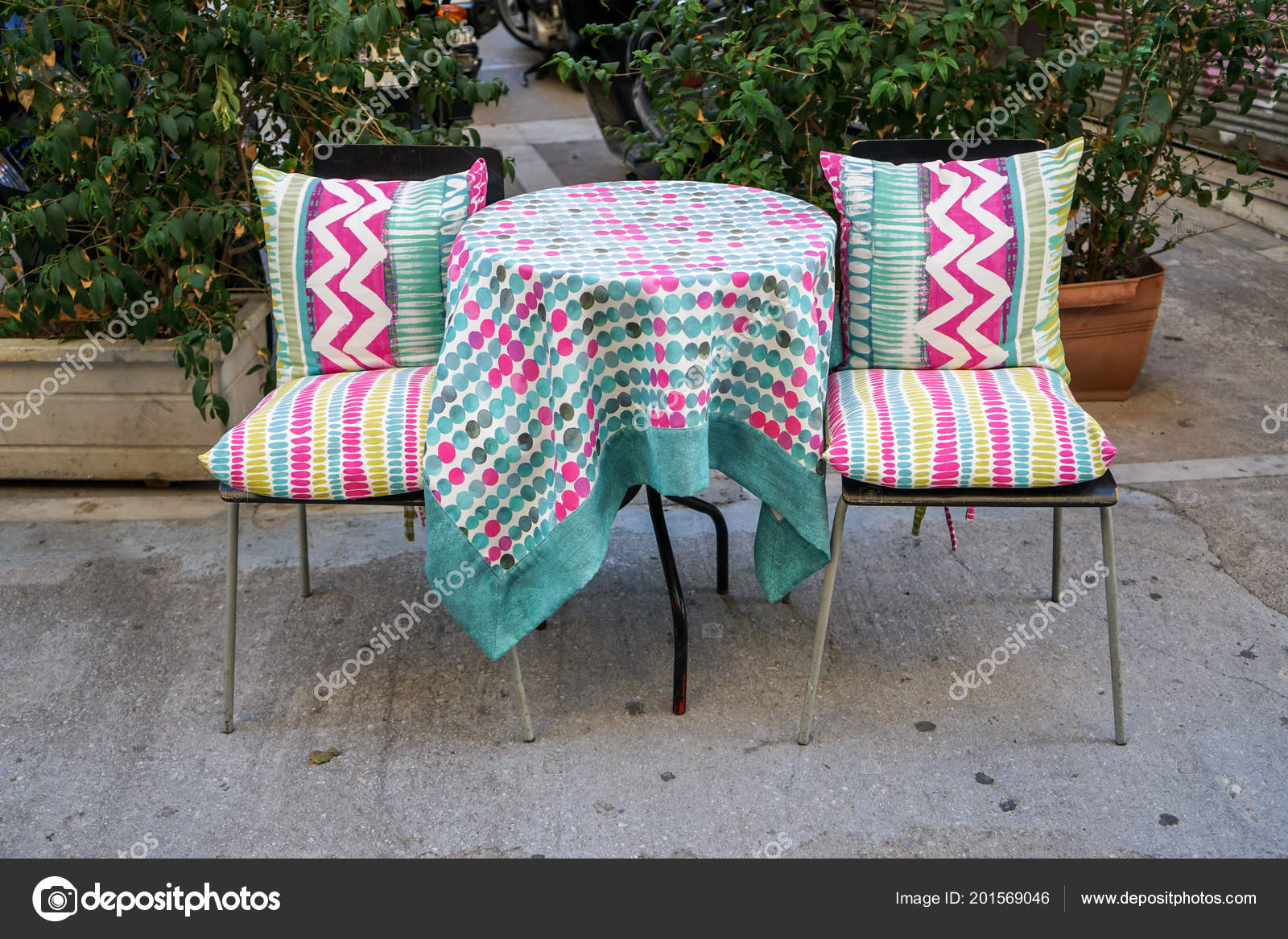 Outdoor furniture round table and chairs with colorful pattern fabric table cloth on concrete floor with green plant pot background athens greece photo