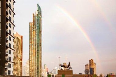 skyscrapers and BTS in Bangkok against rainbow sky