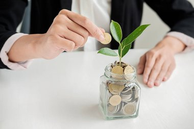 Hands of businessman giving coin to trees growing on coin and banknote. Business growth concept.