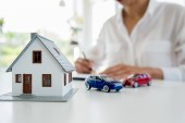 Autó és ház modell ügynök és a vevő megvitatni a szerződést vásárolni, biztosítást, vagy kölcsön ingatlan vagy ingatlan-háttér.