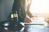 Spravedlnost a zákon pojem. Právní zástupce představuje klientovi podepsanou smlouvu s kladívkem a právní zákon nebo právní s setkání týmu v advokátní kanceláři v pozadí