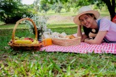 Photo Picnic concept. Happy young asian friends having fun while eating and drinking at a picnic. Enjoying outdoor picnic in garden.